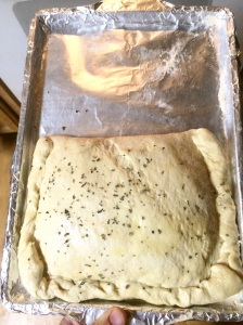 Brush olive oil lightly over dough and sprinkle basil to taste.